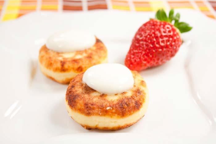 Подавать сырники можно с фруктами. медом, джемом или сметаной
