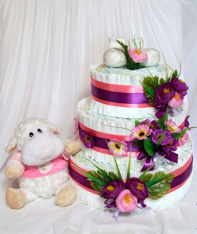 Украсить торт из памперсов можно лентами, цветами, одеждой для новорожденного
